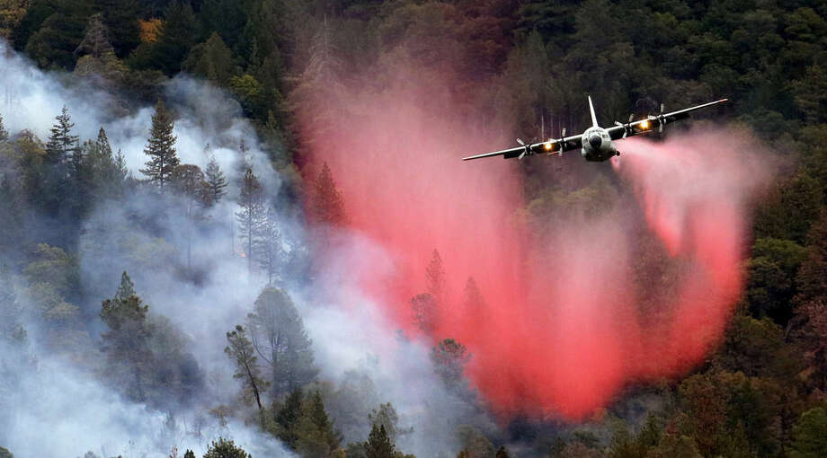 A firefighting plane drops a load of fire retardant over a smoldering hillside Tuesday, Sept. 15, 2015, in Middletown, Calif. The fire that sped through Middletown and other parts of rural Lake County, less than 100 miles north of San Francisco, has continued to burn since Saturday despite a massive firefighting effort. (AP Photo/Elaine Thompson)