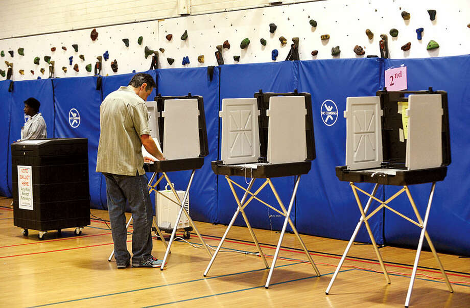 Hour photo / Erik Trautmann A voter casts his ballots in the democratic primary election at Columbus Magnet School Wednesday morning.