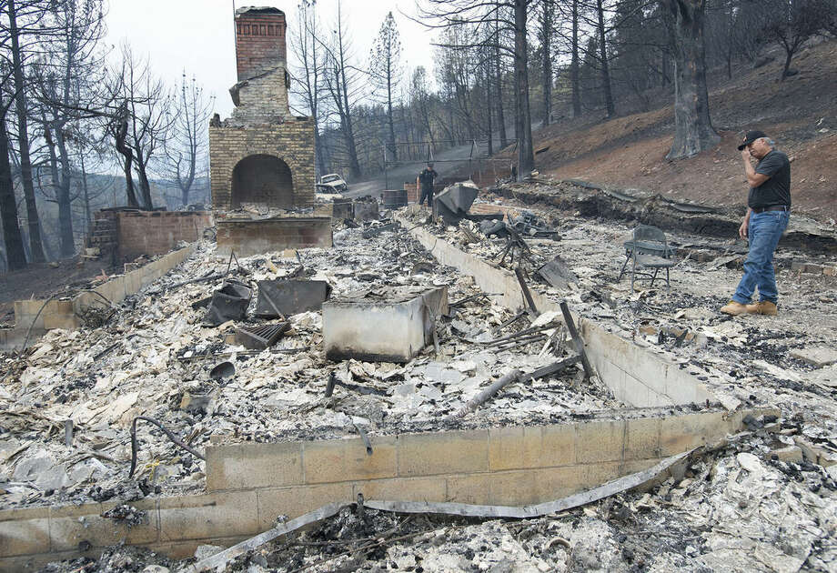 Mike Greenslate stands next to the remains of his home on Tuesday, September 15, 2015, in Lake County, Calif. The fire that sped through Middletown and other parts of rural Lake County, less than 100 miles north of San Francisco, has continued to burn since Saturday despite a massive firefighting effort. (Randy Pench/The Sacramento Bee via AP) MAGS OUT; LOCAL TELEVISION OUT (KCRA3, KXTV10, KOVR13, KUVS19, KMAZ31, KTXL40); MANDATORY CREDIT