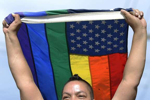 Aleada Minton holds a symbol of gay pride high above her as she walks in the Dyke March in San Francisco, California, on Saturday, June 27, 2015.