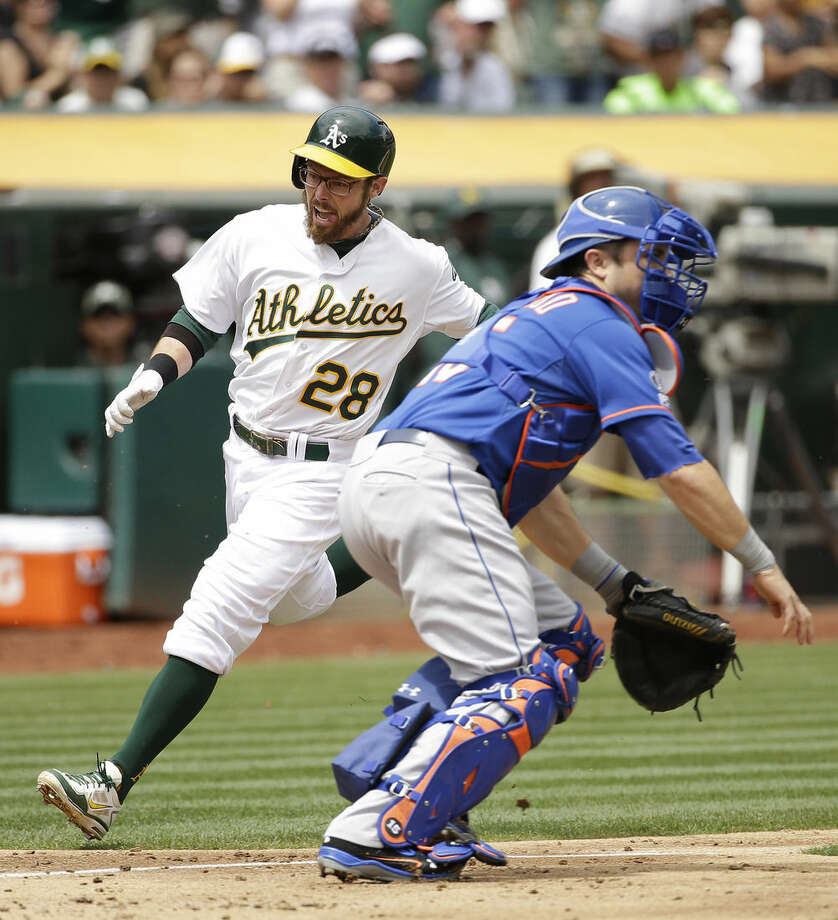 Oakland Athletics' Eric Sogard, left, comes in to score the A's first run as New York Mets catcher Travis d'Arnaud, right, waits for the throw during the third inning of their interleague baseball game Wednesday, Aug. 20, 2014, in Oakland, Calif. Sogard after the Athletics' Coco Crisp doubled. (AP Photo/Eric Risberg)