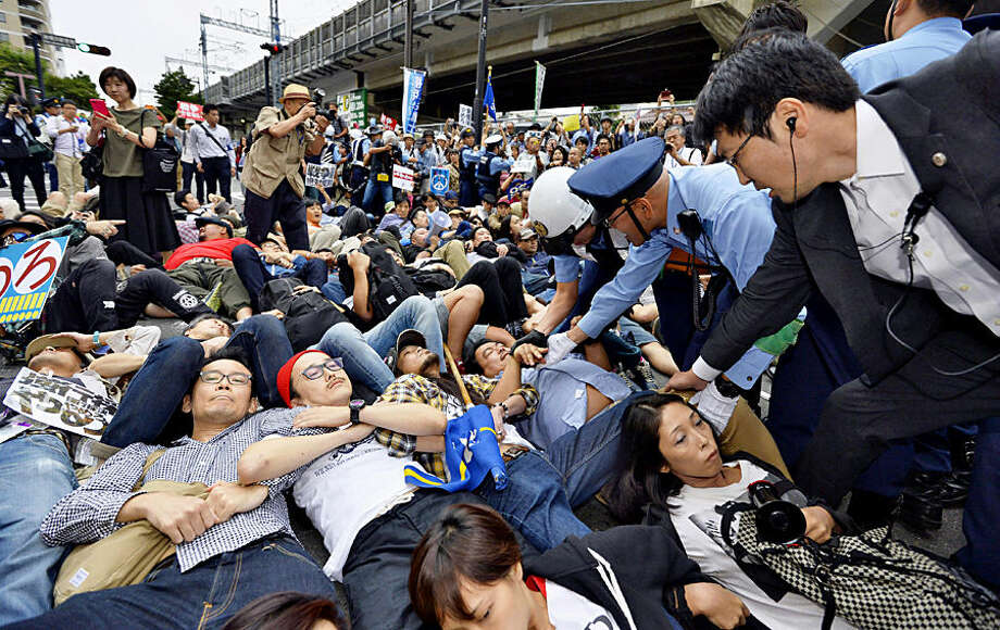Protesters lie down arm in arm as police officers try to clear them in front of the venue hotel for a public hearing on the security legislation in Yokohama, south of Tokyo, Wednesday, Sept. 16, 2015. Opposition lawmakers and thousands of demonstrators were making last-ditch protests in a political showdown Wednesday as Japan's ruling party started a final push to pass security legislation to expand the role of the country's military. (Kyodo News via AP) JAPAN OUT, MANDATORY CREDIT