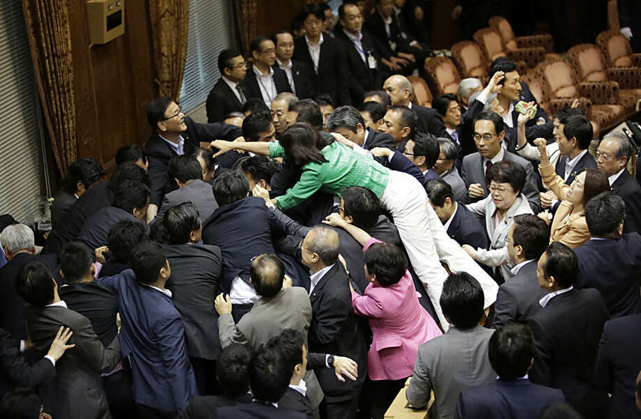 Opposition lawmakers surge toward the chairman's seat to protest as ruling party colleagues rush in to try to protect him during a committee voting of security bills at the upper house of the parliament in Tokyo, Thursday, Sept. 17, 2015. Japan's ruling Liberal Democratic Party pushed contentious security bills through a legislative committee, catching the opposition by surprise and causing chaos in the chamber. If the vote stands, the legislation will go to the upper house of parliament for final approval. (AP Photo/Eugene Hoshiko)