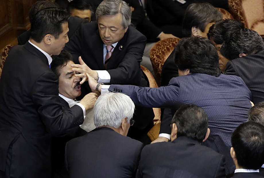 Ruling Liberal Democratic Party Upper House lawmaker Masahisa Sato, second left, acting chairperson of an upper house committee, is blocked to read documents by opposition lawmakers in Tokyo, Thursday, Sept. 17, 2015. Japan's parliament braced Thursday for another battle of wills after opposition lawmakers used delaying tactics to block the committee from meeting to approve bills that would expand the role of the country's military. (AP Photo/Eugene Hoshiko)
