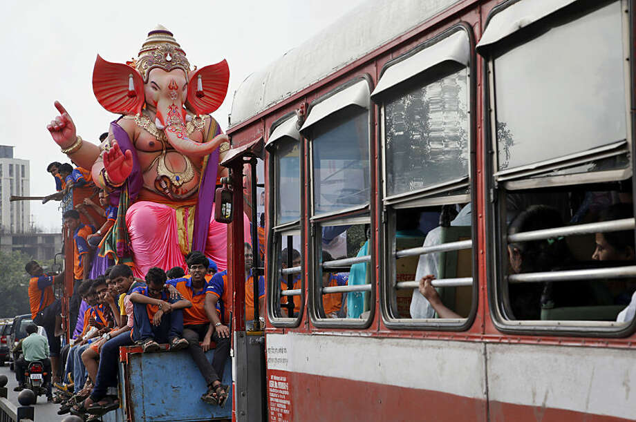 Devotees sit on a truck carrying an idol of elephant-headed Hindu god Ganesha from a workshop ahead of Ganesha Chaturthi festival in Mumbai, India, Wednesday, Sept. 16, 2015. Ganesha Chaturthi, the 10-day festival that celebrates the birth of Ganesha, begins Sept. 17 and ends with the immersion of Ganesha statues in the Arabian Sea and other water bodies. (AP Photo/Rajanish Kakade)