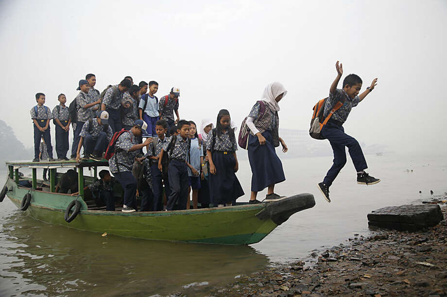 Students prepare to disembark from a boat as they go to school while haze from wildfires blanket the Musi River in Palembang, South Sumatra, Indonesia, Thursday, Sept. 17, 2015. Indonesia intensifies efforts to extinguish the forest fires that cause the haze, which blanketed parts of the archipelago and neighboring countries. (AP Photo/Tatan Syuflana)