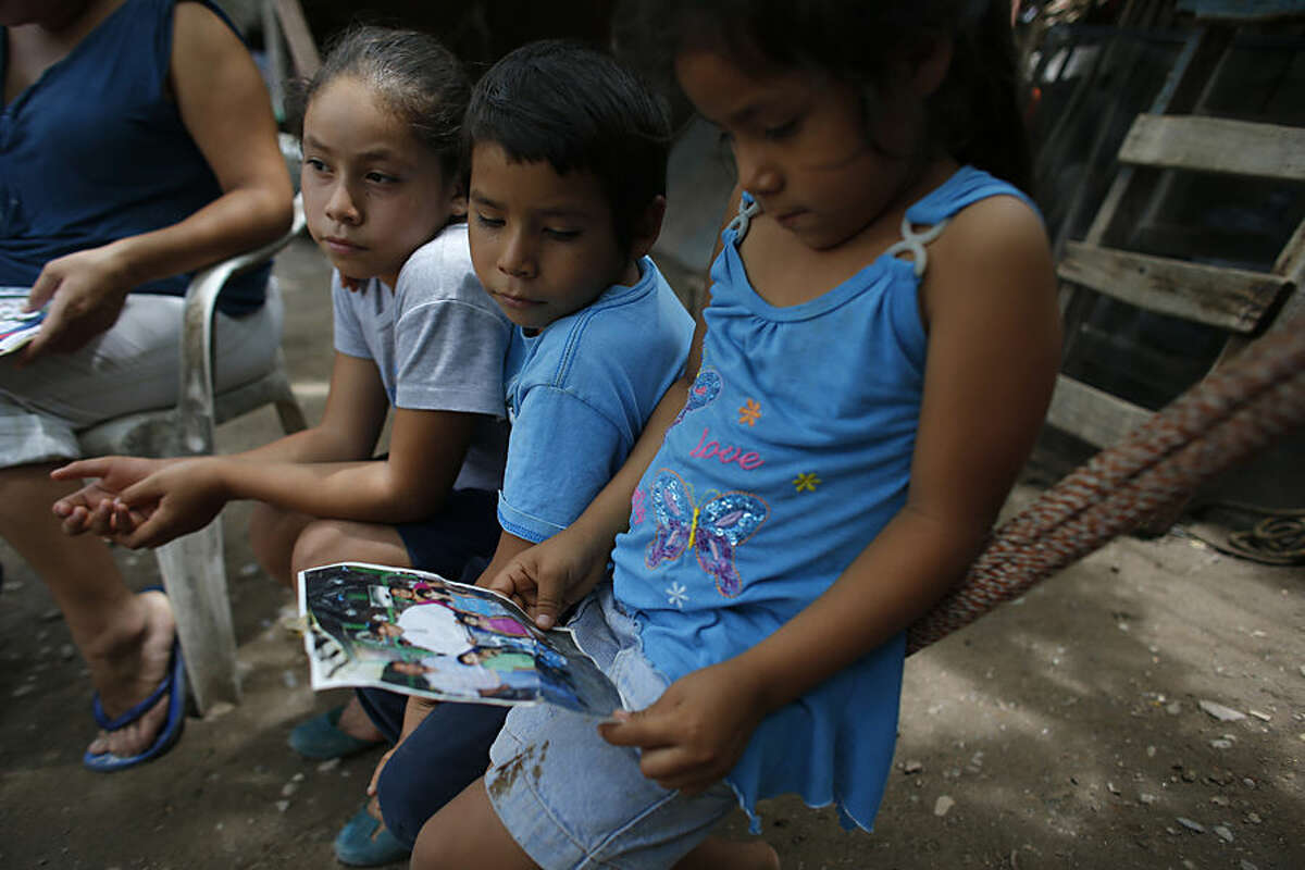 In this June 1, 2015 photo, relatives of Victor Albarran Varela look at a photo of him, at his home in Cocula, Mexico. He is among the 25,000 Mexicans who have disappeared since 2007, according to the government's count. Victor was 15 years old when he was taken on July 1, 2013. (AP Photo/Dario Lopez-Mills)