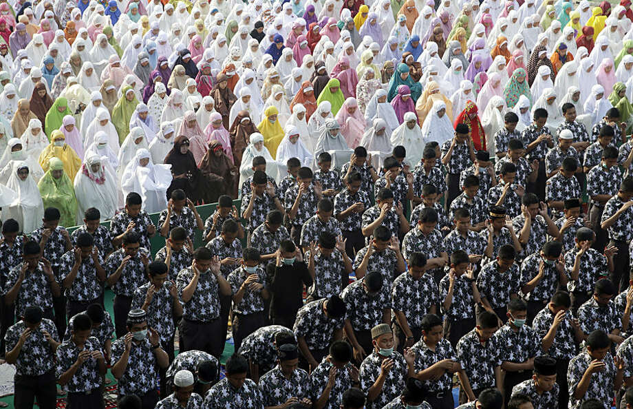 Students pray for rain in Palembang, South Sumatra, Indonesia, Thursday, Sept. 17, 2015. Indonesia intensifies efforts to extinguish the forest fires that cause the haze, which blanketed parts of the archipelago and neighboring countries. (AP Photo/Tatan Syuflana)