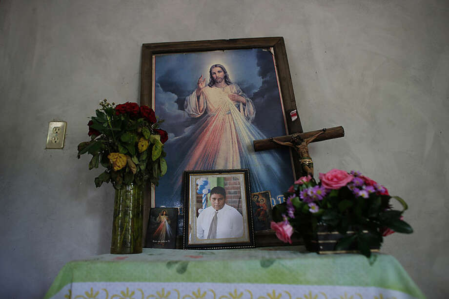 In this June 1, 2015 photo, a framed photo of disapperaed Victor Albarran Varela is surrounded by religious icons on a makeshift altar, in his home in Cocula, Mexico. On July 1, 2013 the explosion of gunfire echoed from the center of this town in the predawn stillness. A convoy of armed men had arrived in town and once they had left, 17 residents including Victor, had disappeared, never to be seen again. They are among the 25,000 Mexicans who have disappeared since 2007, according to the government's count. Victor was 15 years old when he was taken. (AP Photo/Dario Lopez-Mills)