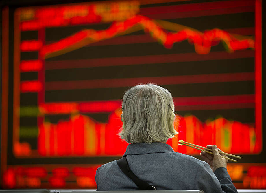 A Chinese investor eats lunch as she monitors stock prices at a brokerage house in Beijing, Wednesday, Sept. 16, 2015. Asian stocks rose Wednesday, tracking gains on Wall Street as investor optimism mounted ahead of a highly anticipated Federal Reserve policy meeting. (AP Photo/Mark Schiefelbein)