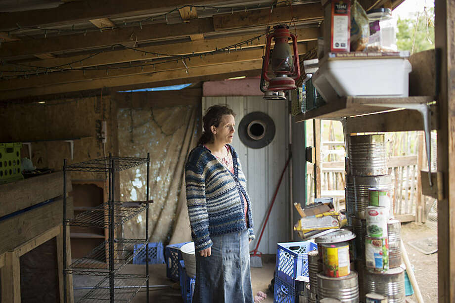 """In this May 21, 2015 photo, Nicole Naugler rests for a moment while she organizes belongings inside her cabin in Garfield, Ky., in the days after the state removed her 10 children and placed them in foster care. Friends and supporters of parents' rights have been helping Naugler and her husband Joe remove garbage from their property and install fencing around their pond. The Nauglers, who call their property a homestead, homeschool their children and do not have running water or electricity and say their simple """"off-grid"""" lifestyle is a choice. (AP Photo/David Stephenson)"""