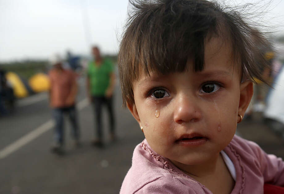 "A girl cries at the ""Horgos 2"" border crossing into Hungary, near Horgos, Serbia, Thursday, Sept. 17, 2015. Thousands of migrants poured into Croatia on Thursday, setting up a new path toward Western Europe after Hungary used tear gas and water cannons to keep them out of its territory. (AP Photo/Darko Vojinovic)"
