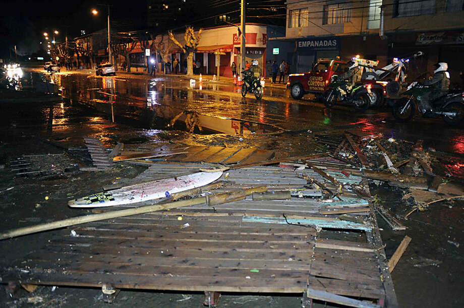Police patrol a debris strewn street in Valparaiso, Chile, after a tsunami, caused by an earthquake hit the area, Wednesday, Sept. 16, 2015. A magnitude-8.3 earthquake hit off Chile's northern coast, causing buildings to sway in Santiago and other cities and sending people running into the streets. Authorities reported one death in a town north of the capital.(Pablo Ovalle Isasmendi/AGENCIA UNO via AP) CHILE OUT - NO USAR EN CHILE