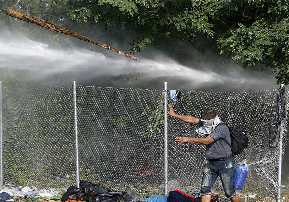 """A migrant throws a piece of wood at Hungarian police at the """"Horgos 2"""" border crossing into the Hungary, near Horgos, Serbia, Wednesday, Sept. 16, 2015. Small groups of migrants continued to sneak into Hungary on Wednesday, a day after the country sealed its border with Serbia and began arresting people trying to breach the razor-wire barrier, while a first group arrived in Croatia seeking another way into the European Union. (AP Photo/Darko Vojinovic)"""
