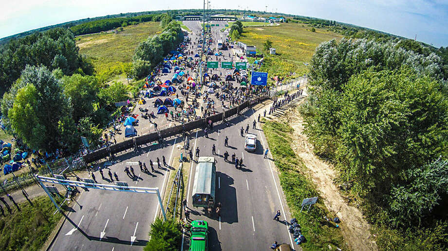 This picture taken by a drone shows the stranded migrants at the border station between Serbia and Hungary near Horgos, Serbia, Wednesday, Sept. 16, 2015. Small groups of migrants continued to sneak into Hungary on Wednesday, a day after the country sealed its border with Serbia and began arresting people trying to breach the razor-wire barrier, while a first group arrived in Croatia seeking another way into the European Union. (Istvan Ruzsa/MTI via AP)