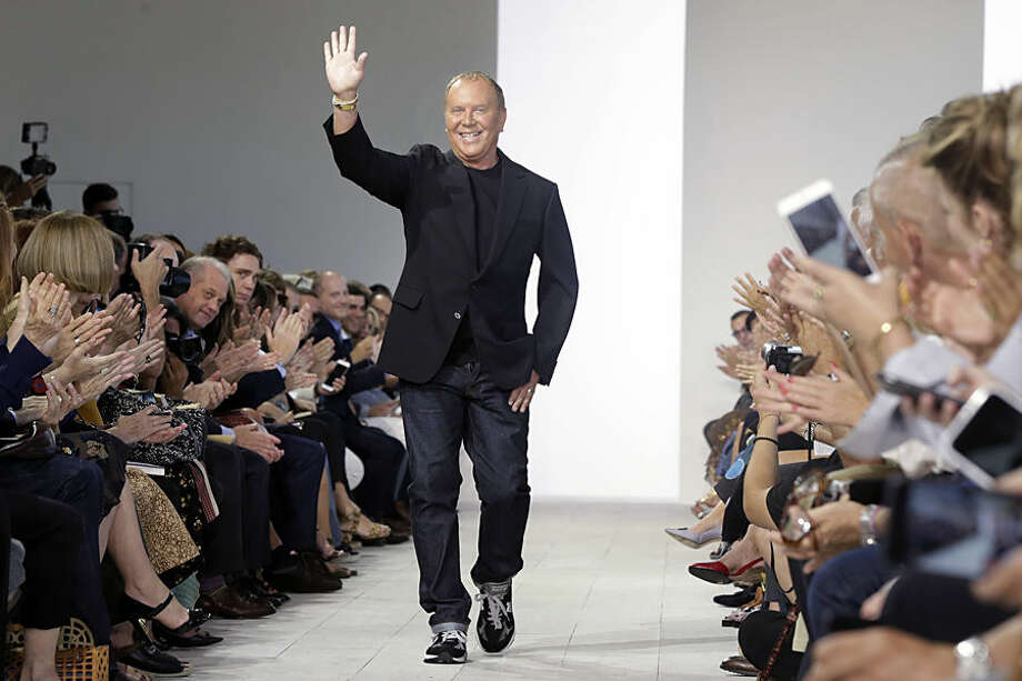 Designer Michael Kors waves to the audience after his Spring 2016 collection was modeled during Fashion Week, in New York, Wednesday, Sept. 16, 2015. (AP Photo/Richard Drew)