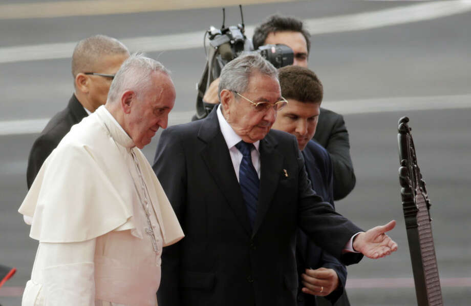Pope Francis is escorted to a chair by Cuba's President Raul Castro during his arrival ceremony at the airport in Havana, Cuba, Saturday, Sept. 19, 2015. Pope Francis begins a 10-day trip to Cuba and the United States on Saturday, embarking on his first trip to the onetime Cold War foes after helping to nudge forward their historic rapprochement. (AP Photo/Ramon Espinosa)