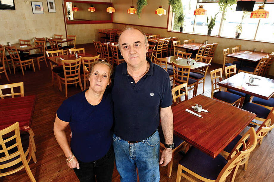 Hour photo / Erik Trautmann Cosmos Pizza restaurant owner Jimmy Tsinois and his employee for over 25 years Lisa Algeria. Norwalk pizza restaurant Cosmos will be closing it's doors this Sunday.