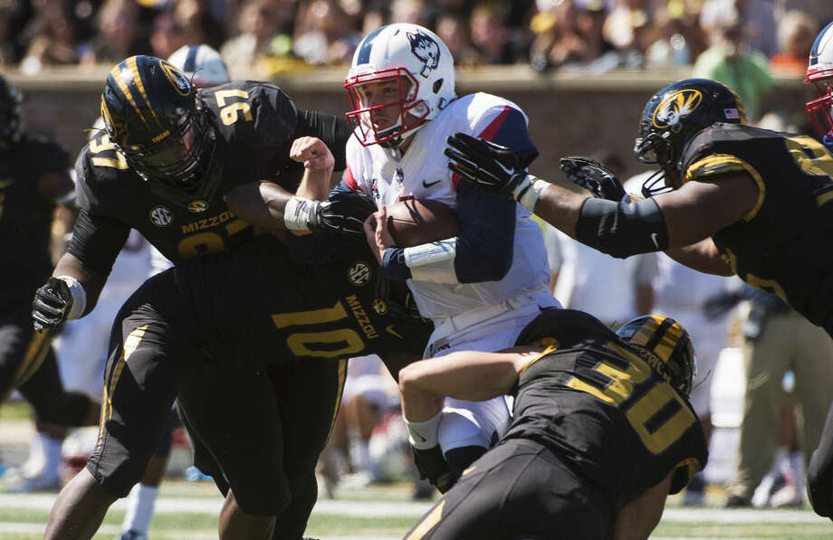 Connecticut quarterback Bryant Shirreffs, center, is gang tackled by Missouri's Rickey Hatley, right, Josh Augusta, left, Michael Scherer (30) and Kentrell Brothers (10) during the fourth quarter of an NCAA college football game Saturday, Sept. 19, 2015, in Columbia, Mo. Missouri won the game 9-6. (AP Photo/L.G. Patterson)
