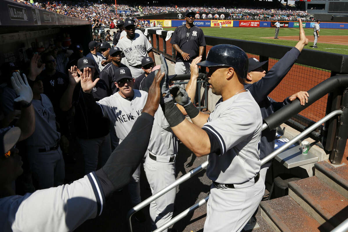 New York Yankees' Carlos Beltran, right, is congratulated by teammates after hitting a three run home run off New York Mets starting pitcher Noah Syndergaard during the first inning of a baseball game, Saturday, Sept. 19, 2015, in New York. (AP Photo/Julio Cortez)
