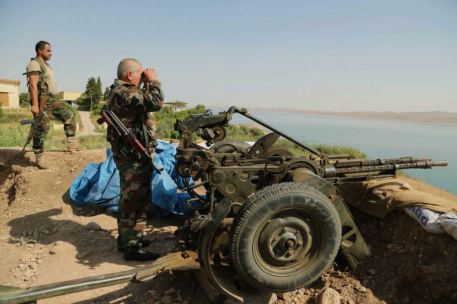 Kurdish forces, known as peshmerga, stand guard near Mosul Dam at the town of Chamibarakat outside Mosul, Iraq, Sunday, Aug. 17, 2014. Kurdish forces took over parts of the largest dam in Iraq on Sunday less than two weeks after it was captured by the Islamic State extremist group, Kurdish security officials said, as U.S. and Iraqi planes aided their advance by bombing militant targets near the facility. (AP Photo/Khalid Mohammed)