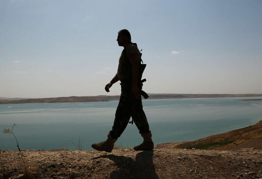 A Kurdish peshmerga fighter patrols near the Mosul Dam at the town of Chamibarakat outside Mosul, Iraq, Sunday, Aug. 17, 2014. Kurdish forces took over parts of the largest dam in Iraq on Sunday less than two weeks after it was captured by the Islamic State extremist group, Kurdish security officials said, as U.S. and Iraqi planes aided their advance by bombing militant targets near the facility. (AP Photo/Khalid Mohammed)