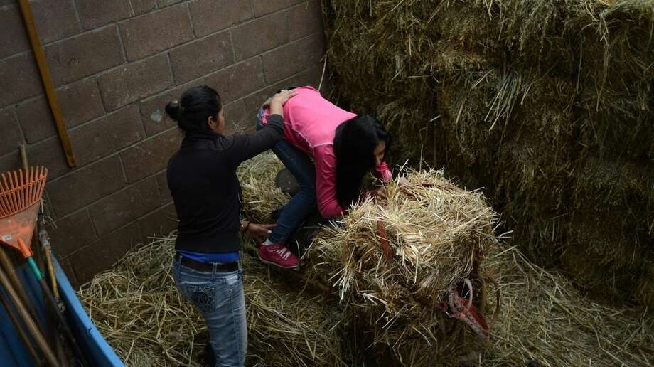 In this July 15, 2014 photo, Elizabeth Garrido, 27, helps Alejandra Luna, 15, to get her posture correct on a mock horse made of hay at the Hippodrome of the Americas in Mexico City. Luna recently left high school to train to be a jockey full-time and hopes to make her debut in the next year. (AP Photo/Sean Havey)