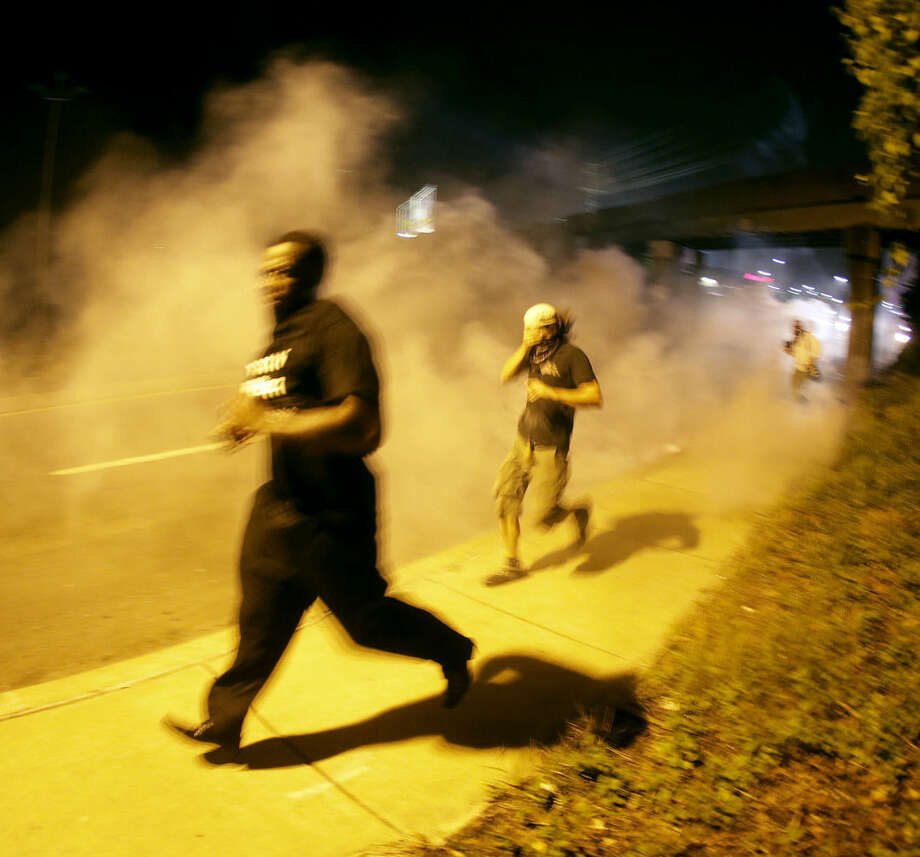 People run from tear gas after police dispersed a crowd Sunday, Aug. 17, 2014, during a protest for Michael Brown, who was killed by a police officer last Saturday in Ferguson, Mo. As night fell Sunday in Ferguson, another peaceful protest quickly deteriorated after marchers pushed toward one end of a street. Police attempted to push them back by firing tear gas and shouting over a bullhorn that the protest was no longer peaceful. (AP Photo/Charlie Riedel)