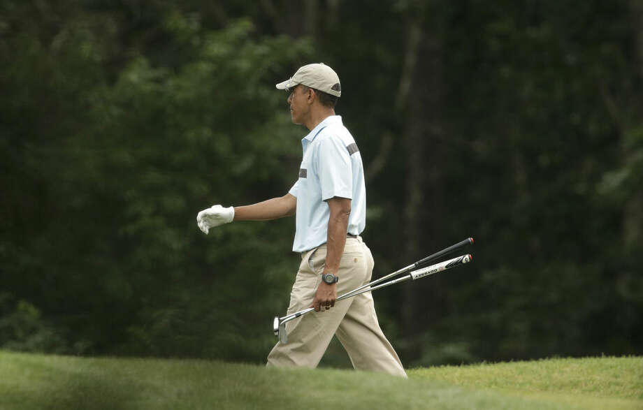 President Barack Obama walks away from a green while golfing at Farm Neck Golf Club, in Oak Bluffs, Mass., on the island of Martha's Vineyard, Sunday, Aug. 17, 2014. In a rare move for him, the president planned a break in the middle of his Martha's Vineyard vacation to return to Washington on Sunday night for unspecified meetings with Vice President Joe Biden and other advisers. (AP Photo/Steven Senne)