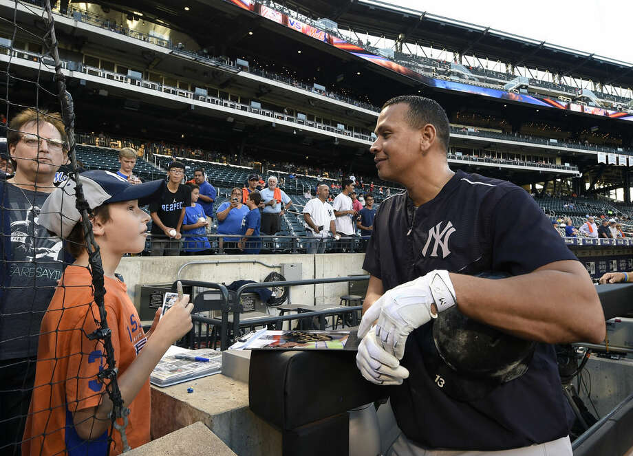 New York Yankees' Alex Rodriguez chats with Alex Weissman, 11, of Livingston, N.J. before signing an autograph for him during batting practice before the interleague baseball game between the New York Yankees and the New York Mets at Citi Field, Friday, Sept. 18, 2015, in New York. (AP Photo/Kathy Kmonicek)