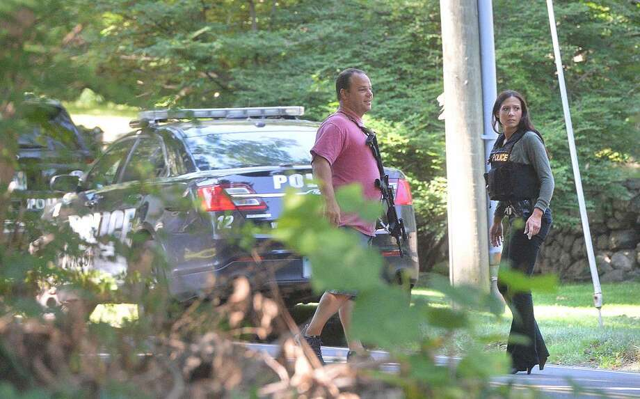Hour Photo/Alex von Kleydorff Westport, Norwalk and Wilton Police search an area off Newtown Tpke on Tuesday morning after a bank was robbed in Westport and the suspects were found in an area off the Merritt parkway