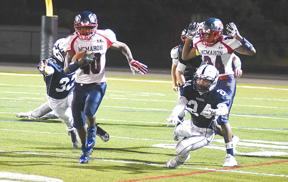 Hour photo/John Nash - Brien McMahon's Jared Fields, left, scampers away from two Wilton tacklers en route to an 89-yard touchdown, his third score of the night, as the Senators defeated Brien McMahon 28-3 at Fujitani Field on Friday night.