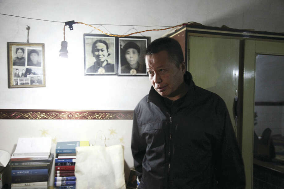 AP photo/Paul TraynorIn this March 15 photo, Gao Zhisheng walks past photos of his relatives in a cave home in northwestern China's Shaanxi province. Leading Chinese rights lawyer Gao said in his first interview in five years that he was tortured with an electric baton to the face and spent three years in solitary confinement during his latest period of detention since 2010.