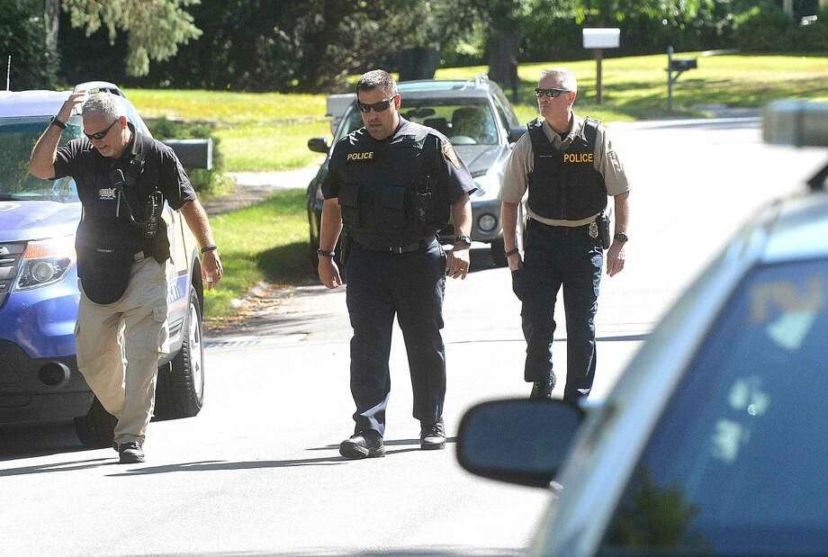Hour Photo/Alex von Kleydorff Norwalk Detectives search an area off Thistle Lane on Tuesday morning after a bank was robbed in Westport and the suspects were found in an area off the Merritt parkway