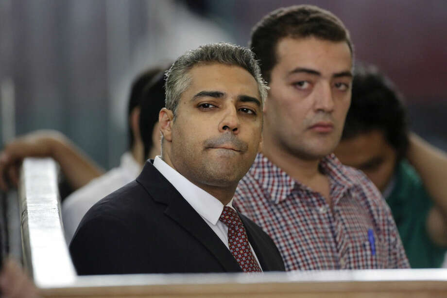 FILE - In this Thursday, June 4, 2015 file photo, Canadian Al-Jazeera English journalist Mohammed Fahmy, left, and his Egyptian colleague Baher Mohammed listen in a courtroom in Tora prison in Cairo, Egypt. A lawyer and Egypt's state-run news agency say President Abdel-Fattah el-Sissi has pardoned a Canadian journalist for Al-Jazeera English, Mohamed Fahmy, and his Egyptian colleague Baher Mohammed, along with prominent human rights activists. (AP Photo/Amr Nabil, File)
