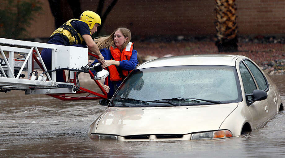 Tucson Fire Department personnel use a ladder truck to rescue a woman from a car stranded in rising flood waters in east Tucson, Ariz., Tuesday, Aug. 19, 2014. (AP Photo/Arizona Daily Star, Kelly Presnell) ALL LOCAL TELEVISION OUT; PAC-12 OUT; MANDATORY CREDIT