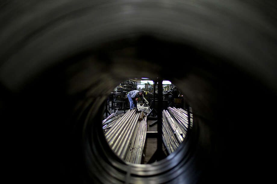 In this Aug. 11, 2014 photo, a worker stands on pipes inside the Work Cooperative Los Constituyentes Limited metallurgical plant, which was formed by steel workers in response to the 2001 economic crisis, in Buenos Aires, Argentina. The president of the cooperative, Felipe Capozzolo, says no one has lost their jobs at the plant, but that working hours were reduced due to less demand. Meanwhile, thousands of employees in the automotive, steel and meat industries have lost their jobs after Argentina was forced into a default in July. (AP Photo/Natacha Pisarenko)
