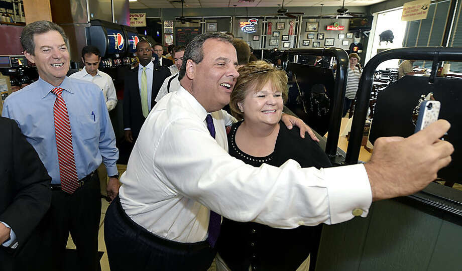 Susan Beauchaine, right, from Overland Park, Kan., stops to get a picture with New Jersey Gov. Chris Christie as Kansas Gov. Sam Brownback, left, looks on at Oklahoma Joe's BBQ Wednesday, Aug. 20, 2014, in Kansas City, Kan. Christie was in town to campaign for Brownback. (AP Photo/The Kansas City Star, John Sleezer)