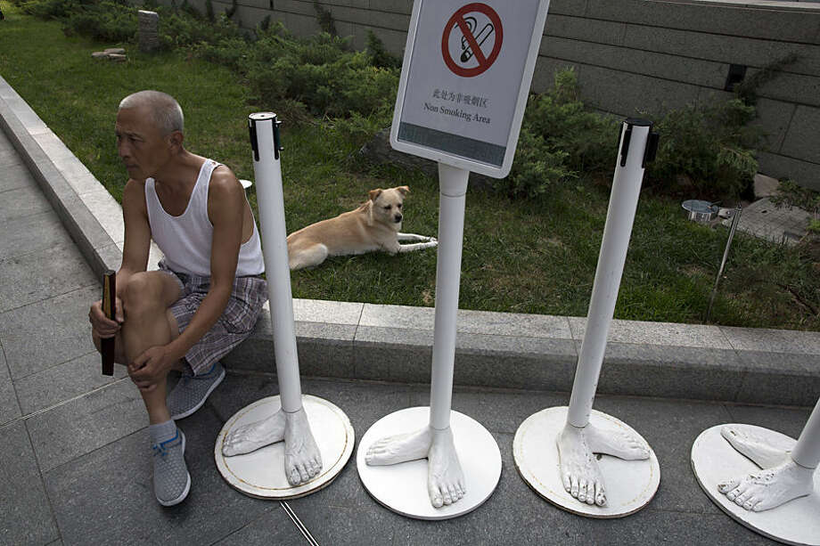 A man rests with a dog near barriers inspired by feet in Beijing, China, Tuesday, Aug. 19, 2014. (AP Photo/Ng Han Guan)