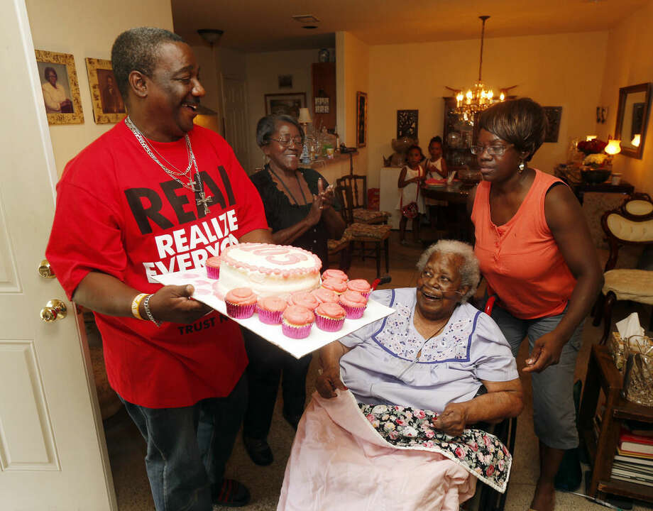 """FILE- In this July 25, 2015, file photo, Terrance Jackson, left, Doris Ware, second from left, and Beverly Booker, right, sing """"Happy Birthday To You"""" to Bernice Williams, seated, as she celebrates her 103rd birthday in the Mill City neighborhood of Dallas. The music publishing company that has been collecting royalties on the song """"Happy Birthday To You"""" for years does not hold a valid copyright on the lyrics to the tune that is one of the mostly widely sung in the world, a federal judge ruled Tuesday, Sept. 22, 2015 (Michael Ainsworth/The Dallas Morning News via AP, File) MANDATORY CREDIT; MAGS OUT; TV OUT; INTERNET USE BY AP MEMBERS ONLY; NO SALES"""