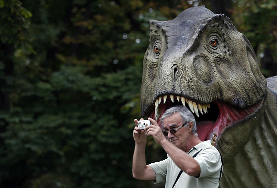 "A visitor takes a picture during the Dinosaurs exhibition in Belgrade, Serbia, Thursday, Aug. 21, 2014. ''Dino Park"" has been opened at Belgrade's Kalemegdan Fortress. (AP Photo/Darko Vojinovic)"