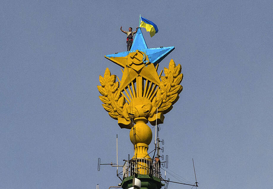A worker takes a selfie before removing a yellow and blue Ukrainian flag attached by protesters atop Stalin-era skyscraper in Moscow, Russia, Wednesday, Aug. 20, 2014. Protesters on Wednesday scaled one of Moscow's famed Stalin-era skyscrapers and painted the Soviet star on its spire in the national colors of Ukraine. The dangerous prank, which set Russian social networking sites abuzz, drew a harsh response from the police.(AP Photo/Ilya Varlamov)