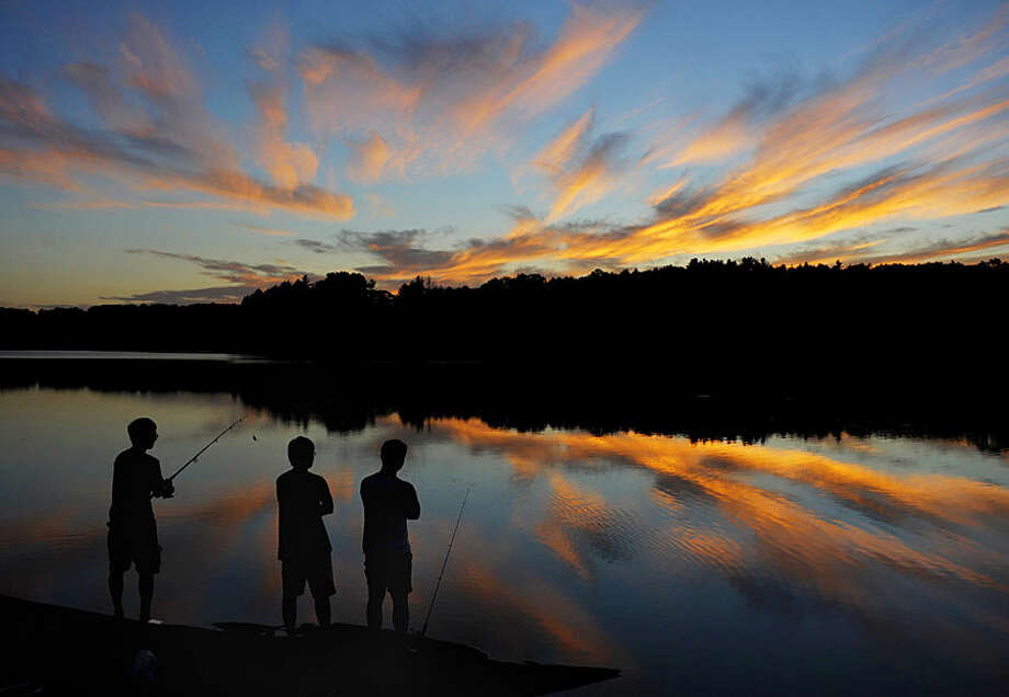 UConn students from Storrs, Conn., Gary Tu, Danny Wang and Victor Zheng, fish at Shenipsit Lake in Tolland, Conn. during sunset on Tuesday, Aug. 19, 2014. (AP Photo/Journal Inquirer, Jim Michaud)