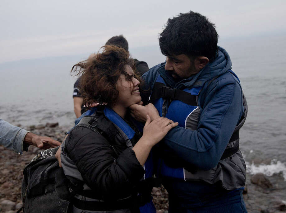A man checks on his wife as they arrive with other migrants on the shores of the Greek island of Lesbos after crossing the Aegean Sea from Turkey on a inflatable dinghy , Tuesday, Sept. 22, 2015. More than 260,000 asylum-seekers have arrived in Greece so far this year, most reaching the country's eastern islands on flimsy rafts or boats from the nearby Turkish coast. (AP Photo/Petros Giannakouris)