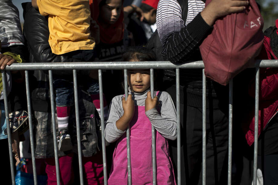 A girl stands behind a barrier as people queue in order to get into a reception center for migrants and refugees in Opatovac, Croatia, Wednesday, Sept. 23, 2015. Deeply divided European Union ministers agreed Tuesday to relocate 120,000 asylum-seekers to ease the strain on Greece and Italy, which are on the front line of the migrant flood. (AP Photo/Marko Drobnjakovic)