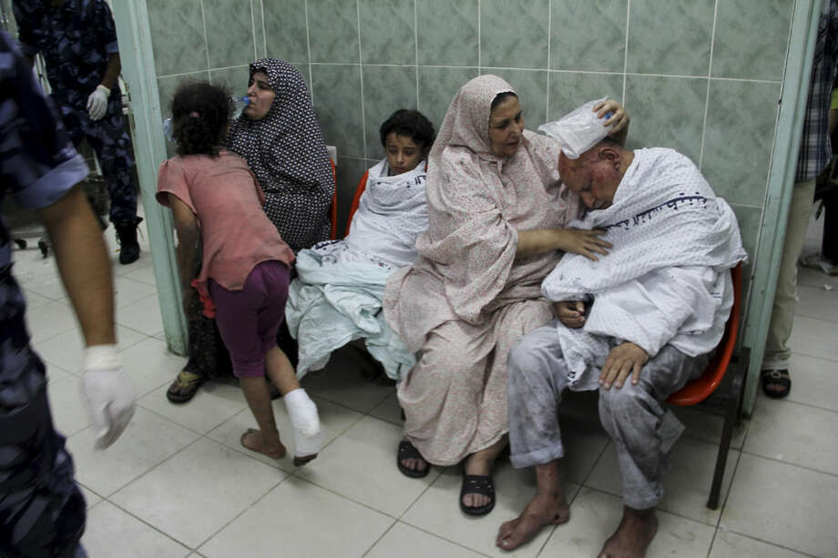 Palestinians wait for treatment, following an Israeli airstrike on a building, at the treatment room of al Najar hospital in Rafah in the southern Gaza Strip, Thursday, Aug. 21, 2014. (AP Photo/Hatem Ali)