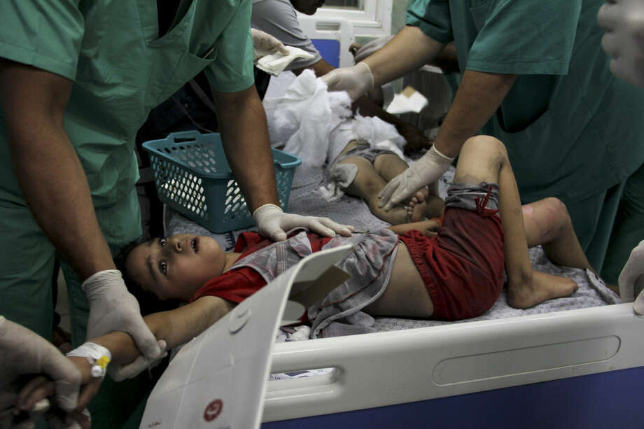 Palestinian doctors treat children wounded in an Israeli airstrike on a building, at the treatment room of al Najar hospital in Rafah in the southern Gaza Strip, Thursday, Aug. 21, 2014. (AP Photo/Hatem Ali)