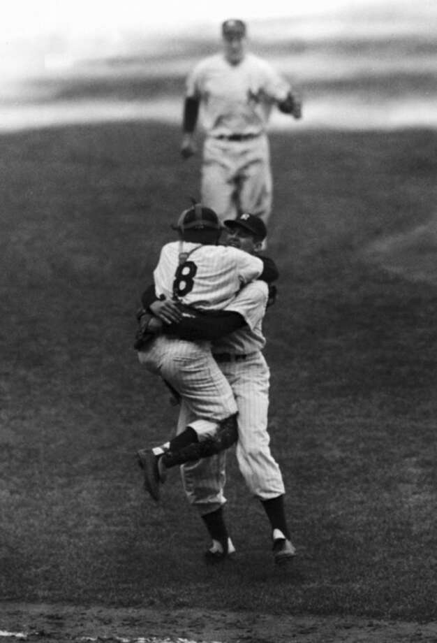 File-This Oct. 8, 1956, file photo shows New York Yankees' catcher Yogi Berra leaping into the arms of pitcher Don Larsen after Larsen struck out the last Brooklyn Dodgers' batter to complete his perfect game during the fifth game of the World Series. Berra, the Yankees Hall of Fame catcher has died. He was 90. (AP Photo/File)