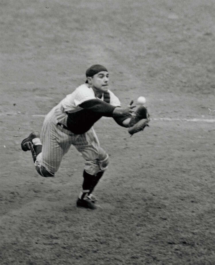File-This Sept. 2, 1962, file photo shows catcher Yogi Berra of the New York Yankees grabbing for a foul pop bunted by pitcher Tony Pena of the Kansas City Athletics in the eighth inning of the game at New York's Yankee Stadium. Berra, the Yankees Hall of Fame catcher has died. He was 90. (AP Photo/File)