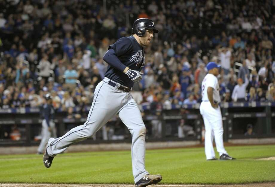 Atlanta Braves' Freddie Freeman rounds the bases after hitting a three-run home run off New York Mets pitcher Jeurys Familia, right, during the ninth inning of a baseball game Wednesday, Sept. 23, 2015, in New York. The Braves defeated the Mets 6-3. (AP Photo/Bill Kostroun)